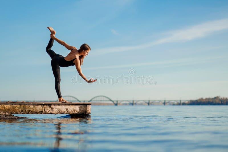 在安静的木码头的年轻女人实践的瑜伽锻炼有城市背景 体育和休闲在城市仓促 免版税库存图片