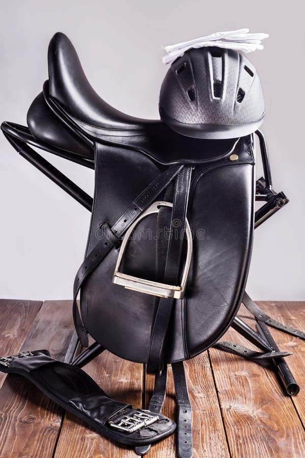 在完全的黑专业皮革驯马马鞍与骑马盔甲和手套 库存照片