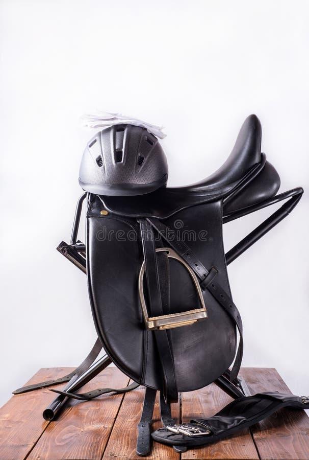 在完全的黑专业皮革驯马马鞍与骑马盔甲和手套puted在马鞍机架旅行 库存照片