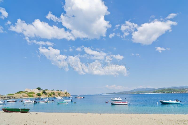 在完善的云彩下,小船在海滩的一个小钓鱼海港在Sithonia 免版税库存图片