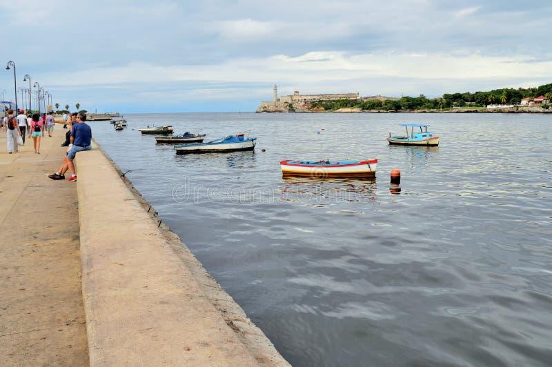 在定住在Malecon江边附近,海海峡、El Morro堡垒和开放海洋,哈瓦那,古巴的看法的Ishing小船 免版税图库摄影