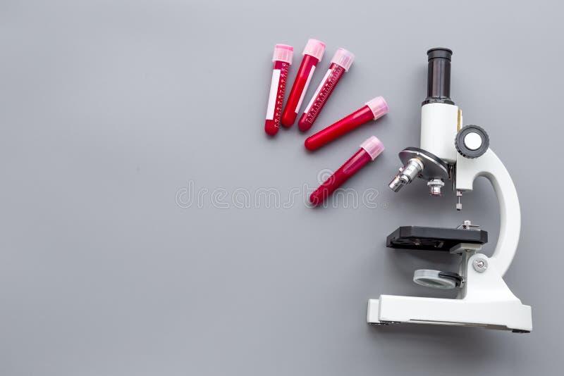 在实验室做验血 无政府主义 在试管的血样在灰色背景顶视图的显微镜附近复制 库存照片
