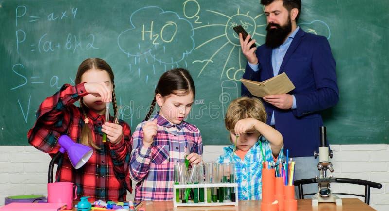 在实验室外套的孩子学会化学的在学校实验室 化学实验室 愉快的儿童老师 r ? 免版税库存照片