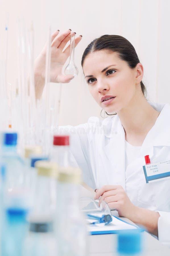 年轻在实验室的科学家reseaching的水 库存图片