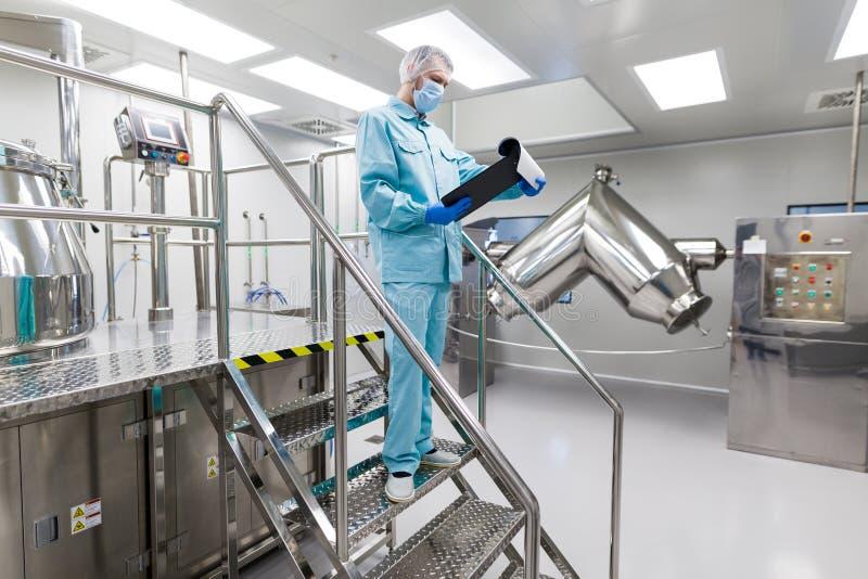 在实验室种植图片,科学家站立在梯子,检查读书 免版税库存图片
