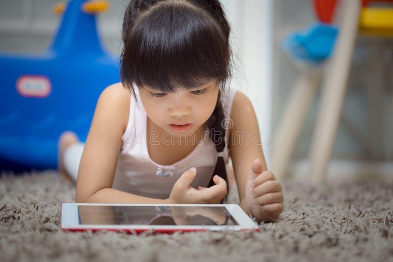 在客厅地毯的儿童游戏片剂 免版税图库摄影