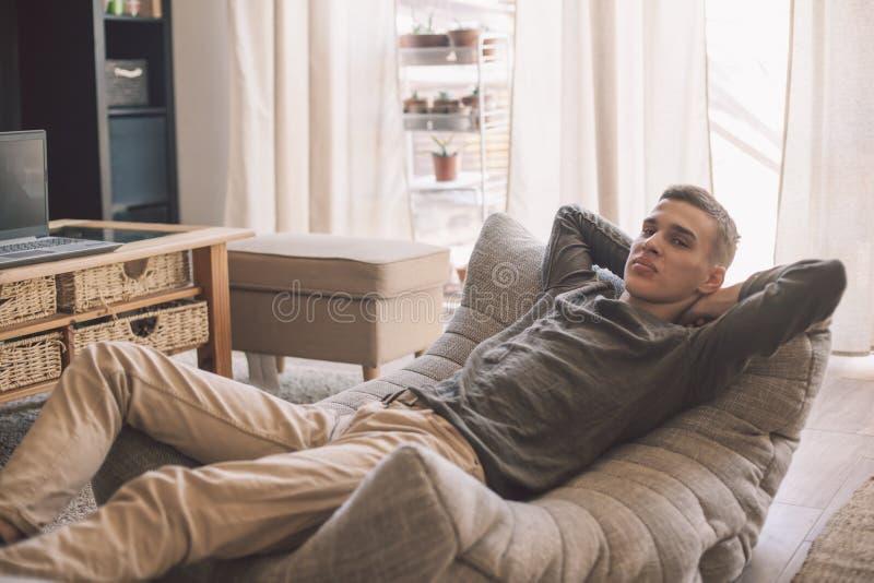 在客厅里,帅气的少年男人在现代柔软的沙发上放松 图库摄影