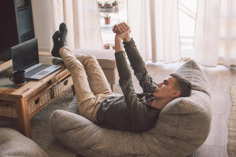 在客厅里,帅气的少年男人在现代柔软的沙发上放松 免版税库存照片