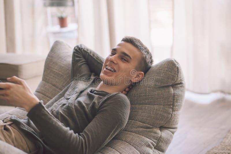 在客厅里,帅气的少年男人在现代柔软的沙发上放松 库存图片