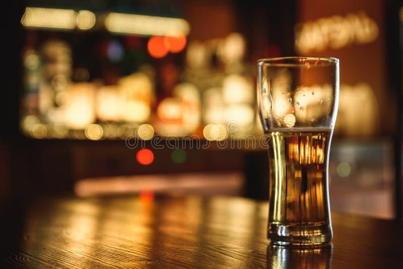 在客栈背景的低度黄啤酒 免版税库存图片