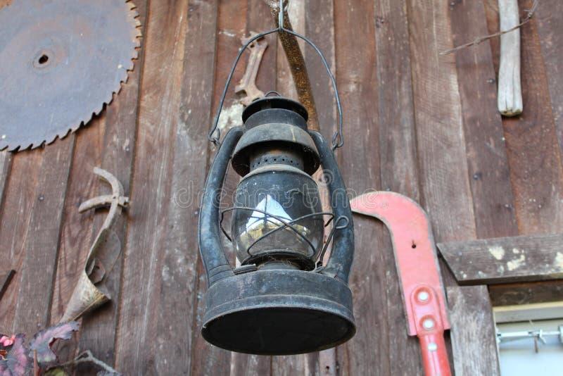 在客舱墙壁上的老灯笼和农厂工具 库存照片