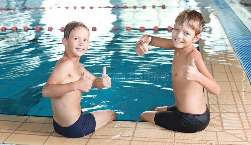 在室内游泳池附近的逗人喜爱的小男孩 免版税库存图片