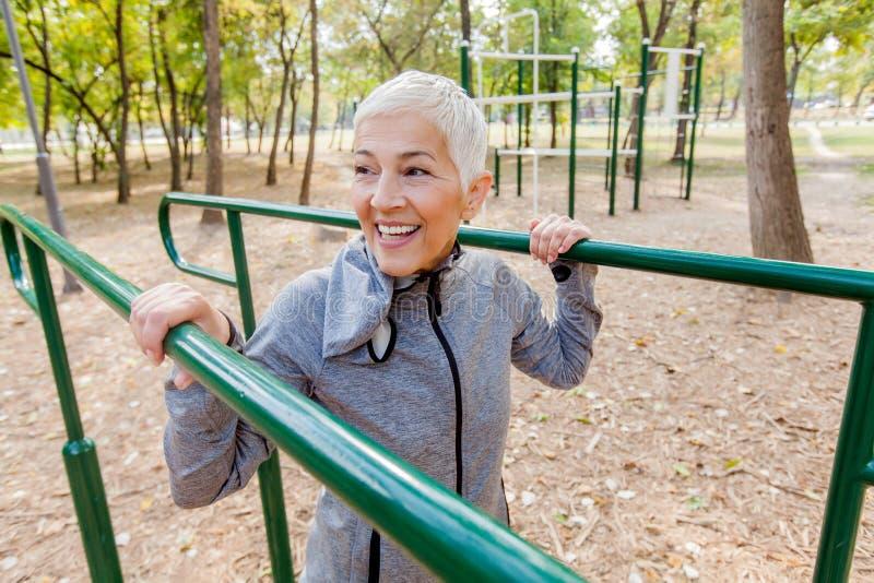 在室外健身房的微笑的成熟妇女锻炼 库存图片