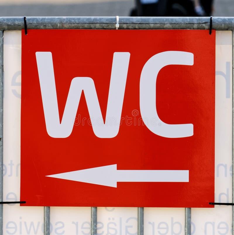 """在室外区域的红色标志在与白色书面标志""""的一个节日; WC'并且指向往洗手间的箭头 免版税库存图片"""
