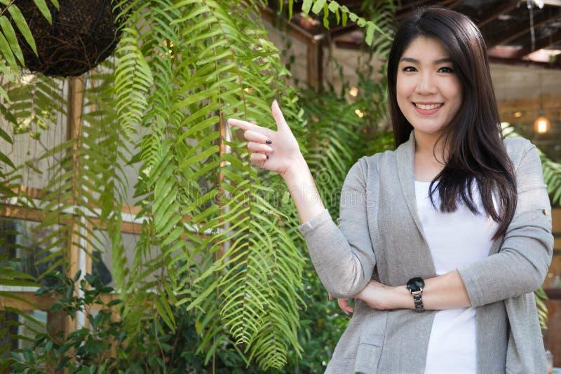 在室外咖啡馆的亚洲妇女姿势 与natura的年轻女性成人 免版税库存照片