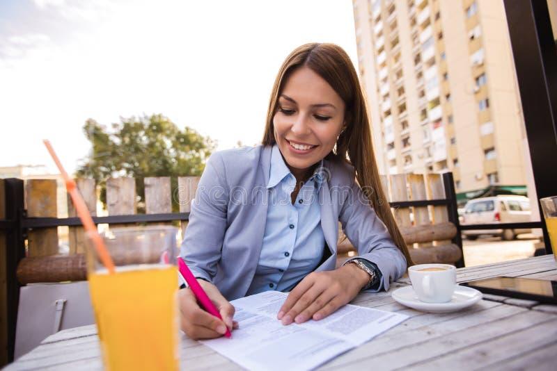 在室外咖啡馆的年轻女实业家候宰栏 图库摄影