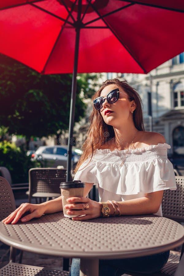 在室外咖啡馆的美丽的时髦的少妇饮用的咖啡在夏天 时装模特儿佩带的夏天成套装备 免版税库存图片