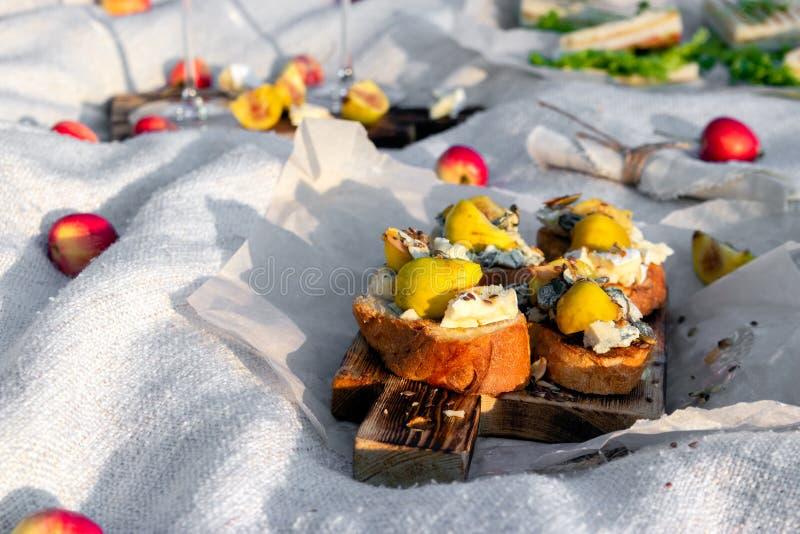 在室外夏天或春天野餐的食物在晴朗的草甸的森林里,bruschetta用乳酪和梨,快餐,苹果,木板材 库存照片