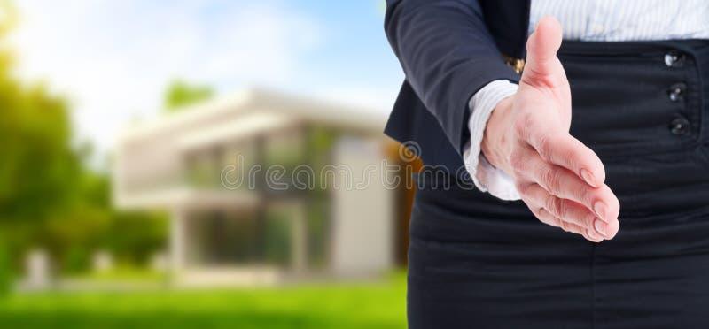 在室外房子背景的握手提议作为房地产conce 库存图片