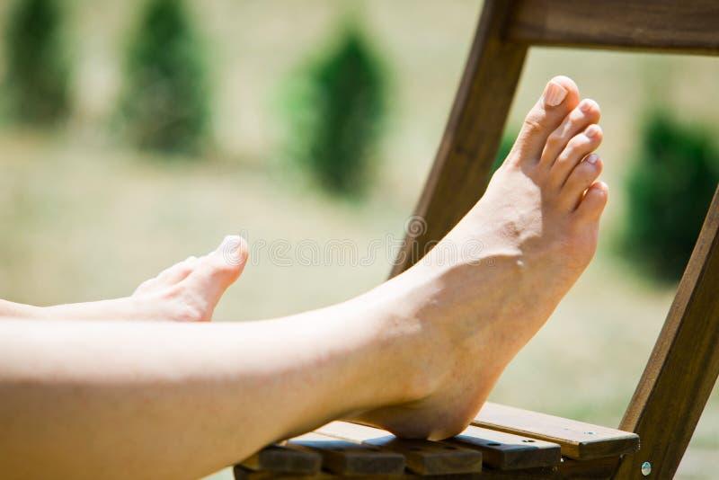 在室外木的椅子的妇女的脚 免版税库存图片