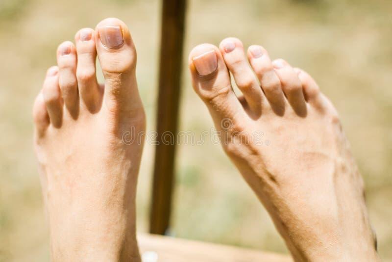 在室外木的椅子的妇女的脚 免版税图库摄影