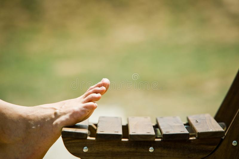 在室外木的椅子的妇女的脚 库存照片