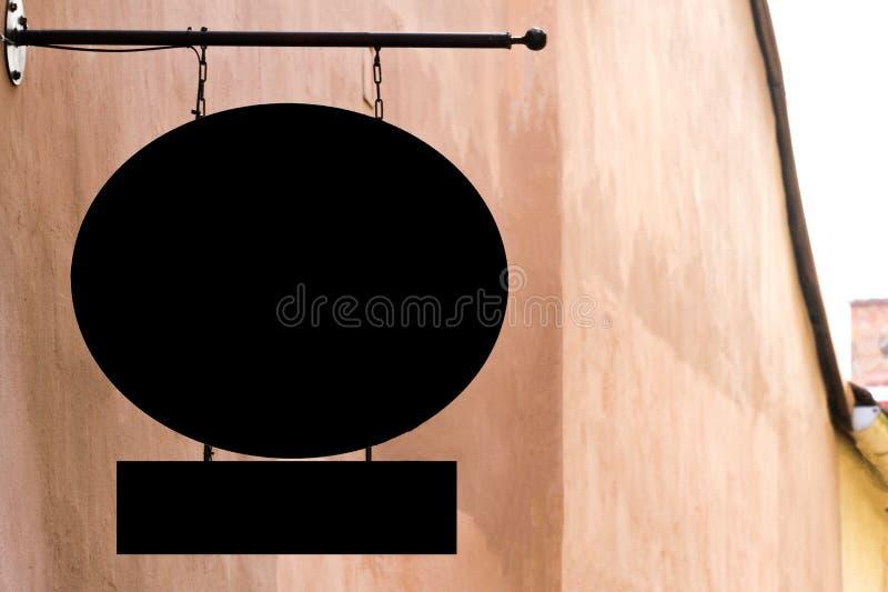 在室外的墙壁上的黑空白的牌,嘲笑  免版税库存照片