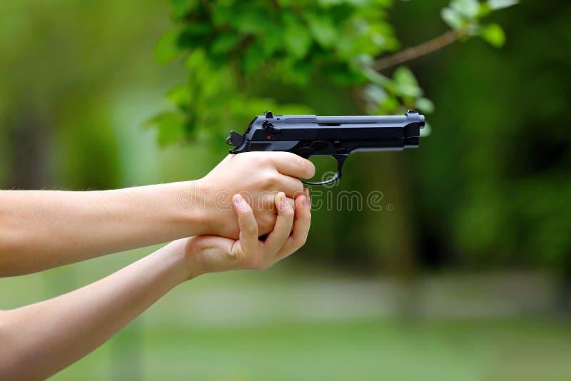 在室外的年轻男孩实践射击枪 库存照片