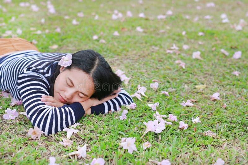 在室外的庭院里放松和充分地说谎在与秋天桃红色花的绿色领域的睡觉的年轻亚裔妇女 免版税库存图片