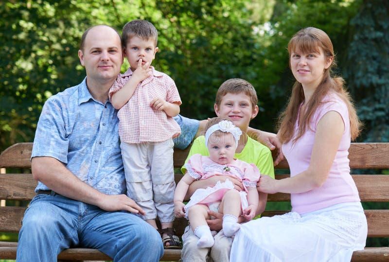 在室外的愉快的家庭画象,小组五个人在城市公园、夏季、孩子和父母坐长木凳 免版税库存图片