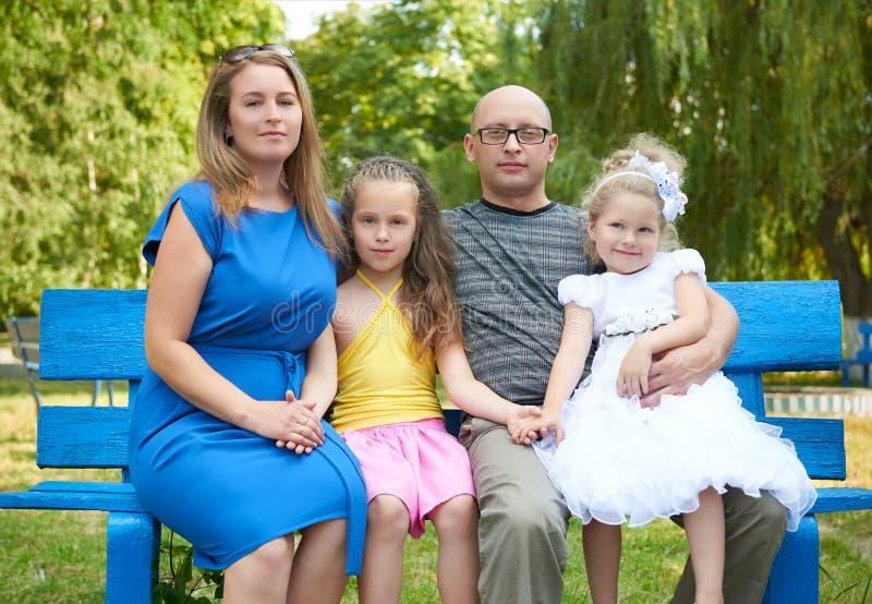 在室外的愉快的家庭画象,小组四个人在城市公园、夏季、孩子和父母坐长木凳 库存图片