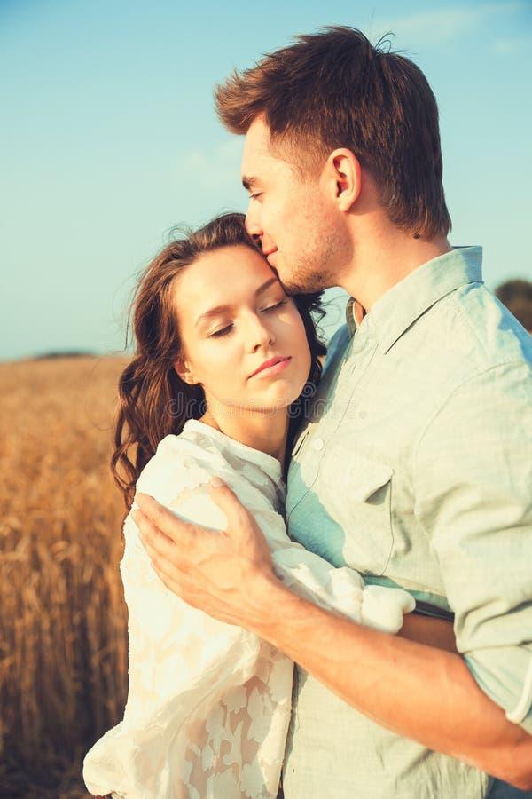 在室外的爱的新夫妇 摆在领域的夏天的年轻时髦的时尚夫妇惊人的肉欲的室外画象  愉快的Smi 免版税库存照片