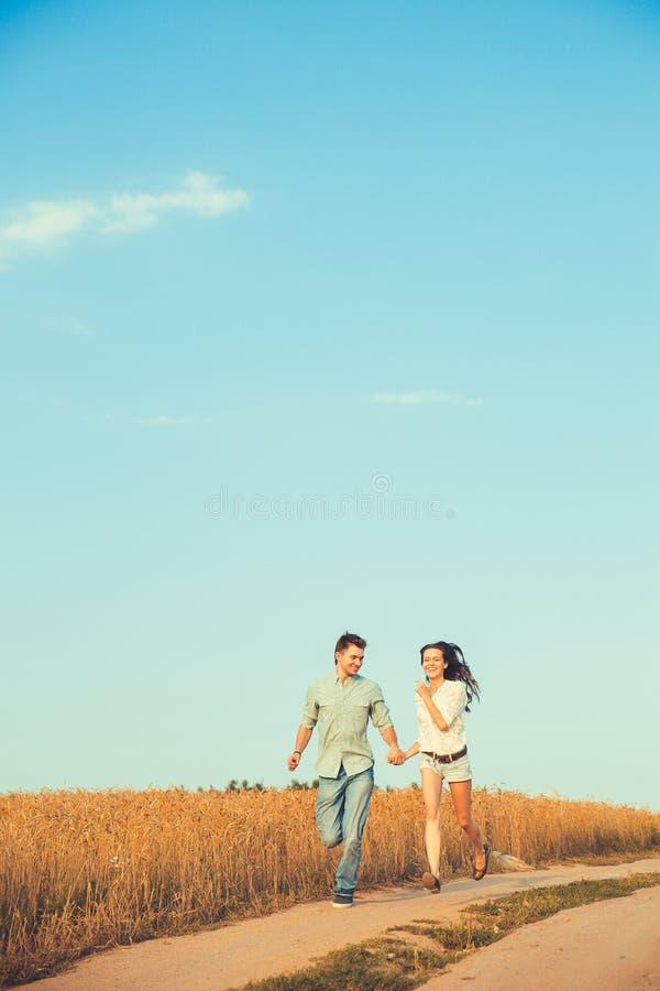 在室外的爱的新夫妇 摆在领域的夏天的年轻时髦的时尚夫妇惊人的肉欲的室外画象  库存图片