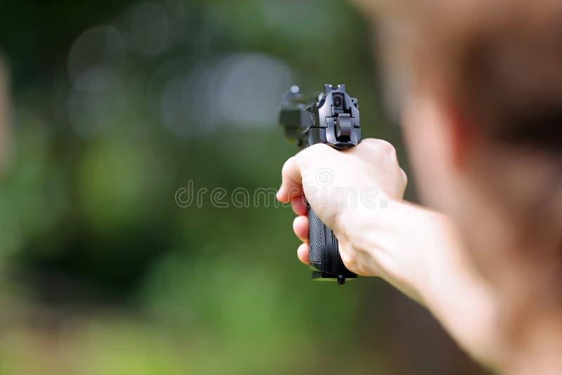 在室外的年轻男孩实践射击枪 免版税库存照片