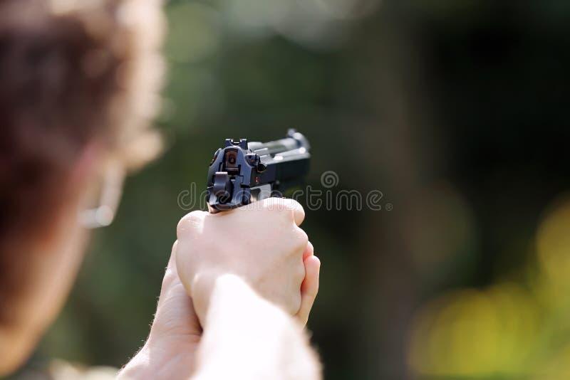 在室外的年轻男孩实践射击枪 免版税库存图片