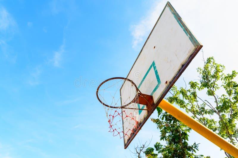 在室外街道法院的老篮球档板 免版税库存图片