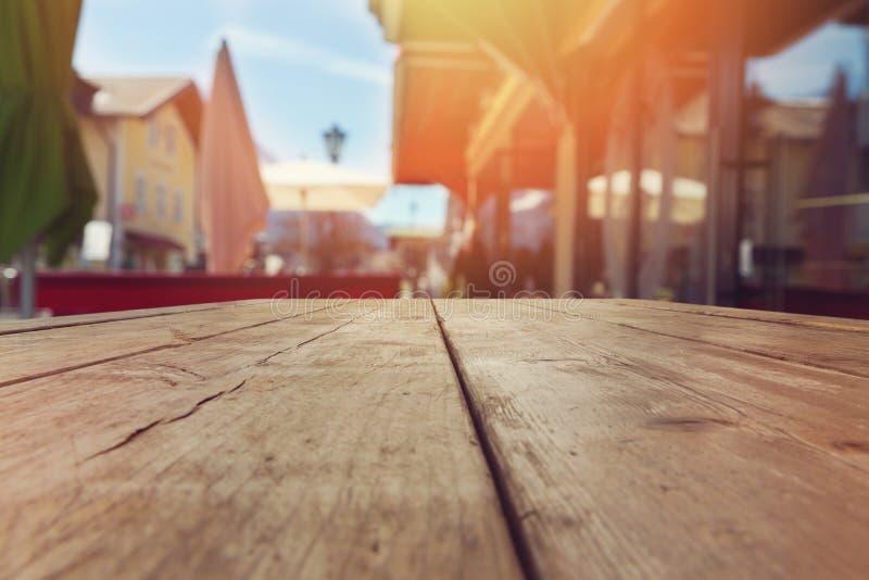 在室外被弄脏的餐馆的空的木土气桌 免版税库存照片