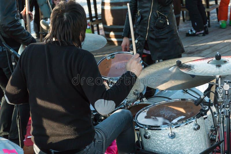 在室外音乐会期间的黑发鼓手:背面图 库存照片