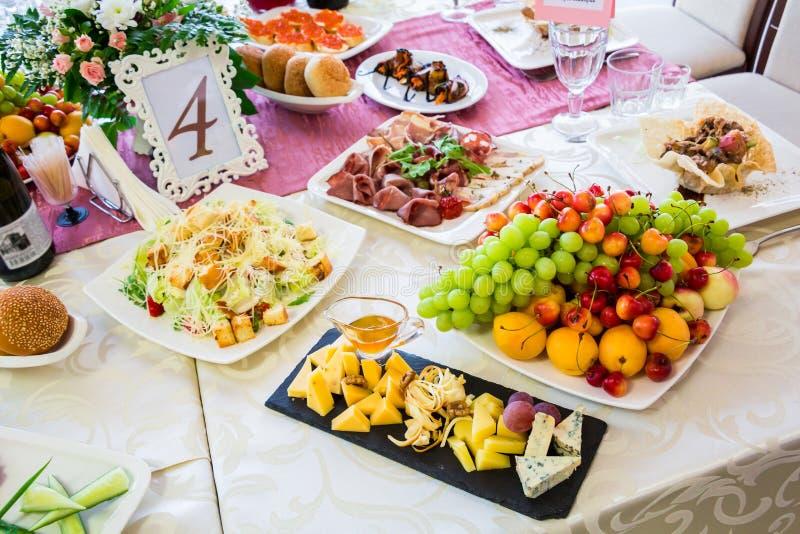 在宴会的服务的桌 果子、快餐、纤巧和花在餐馆 庄严的事件或婚礼 图库摄影