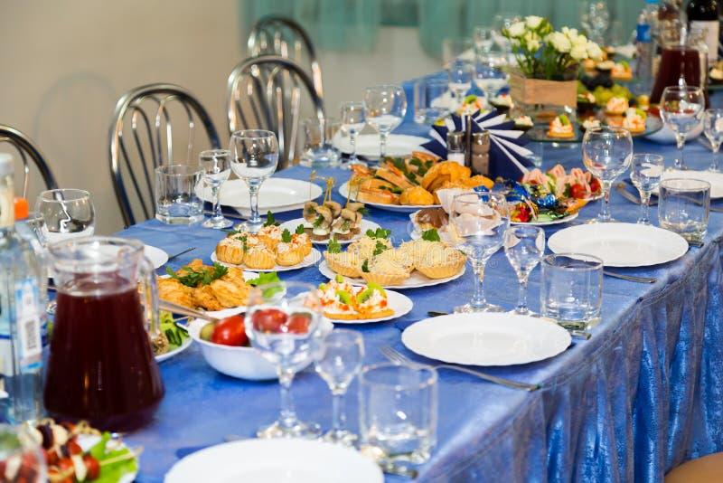 在宴会的服务的桌 饮料、酒精、纤巧和快餐 承办酒席 招待会事件 免版税库存照片