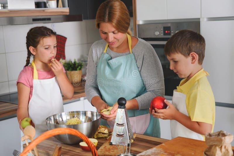 在家一起做苹果饼的母亲和孩子在厨房里 帮助母亲的孩子 库存照片