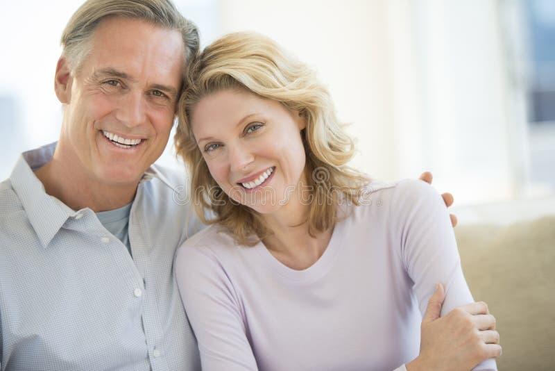 在家一起微笑的夫妇 免版税库存图片