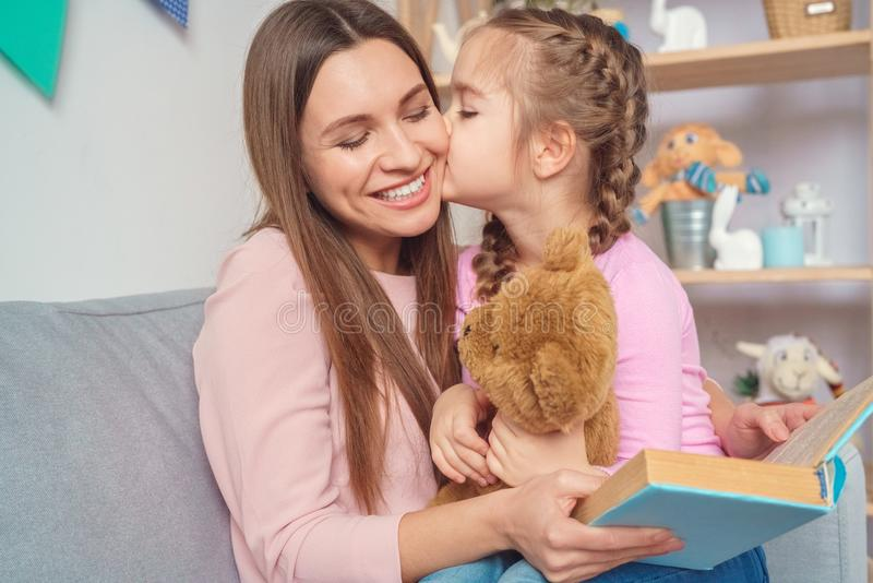 在家一起母亲和女儿妇女对女孩的阅读书 免版税库存图片