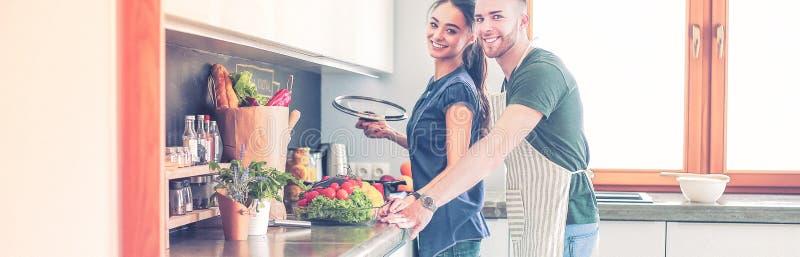 在家一起烹调在他们的厨房里的夫妇 免版税图库摄影