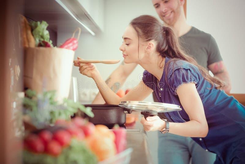 在家一起烹调在他们的厨房里的夫妇 库存照片