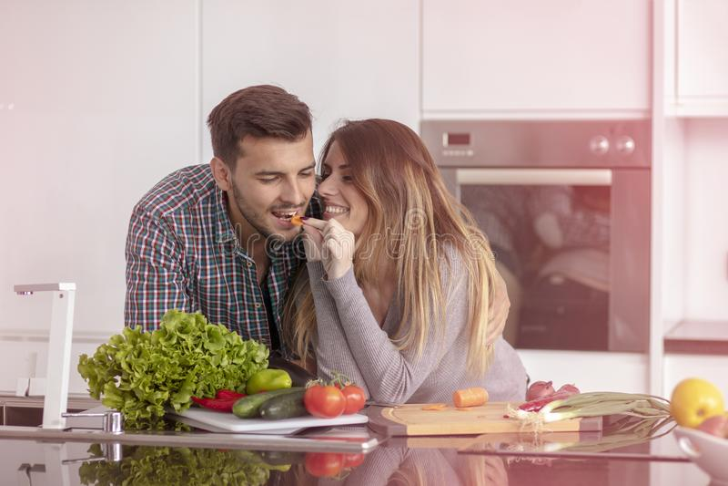 在家一起烹调在厨房里的愉快的年轻夫妇画象  库存照片