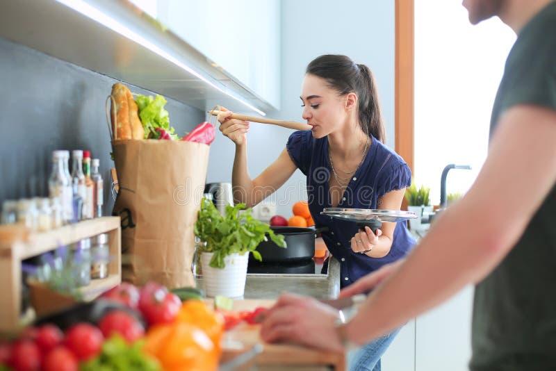 在家一起烹调在他们的厨房里的夫妇 图库摄影