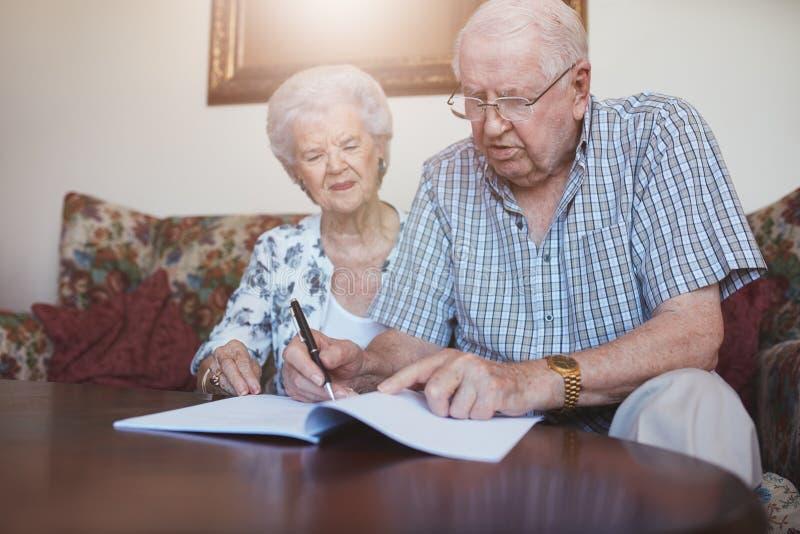 在家一起签署文书工作的资深夫妇 免版税库存图片