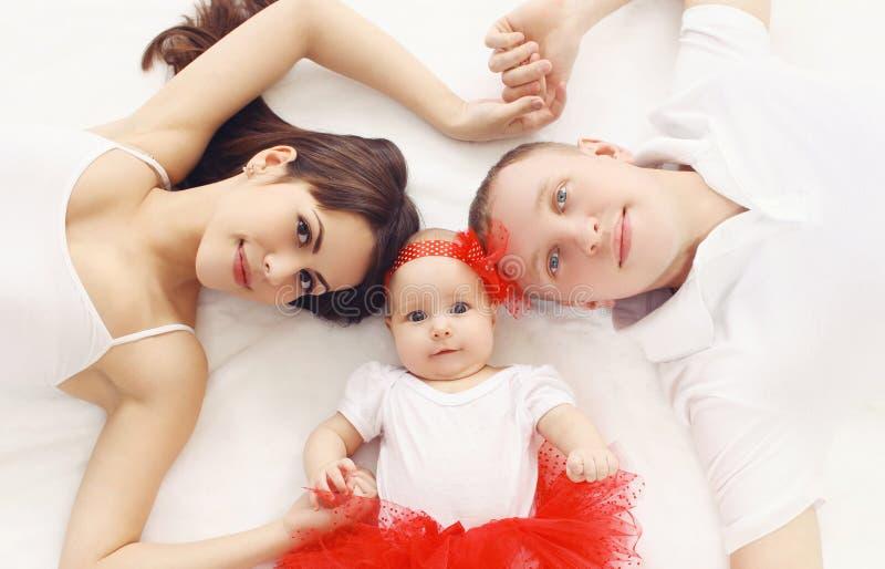 在家一起说谎在床上的愉快的家庭画象 免版税库存照片