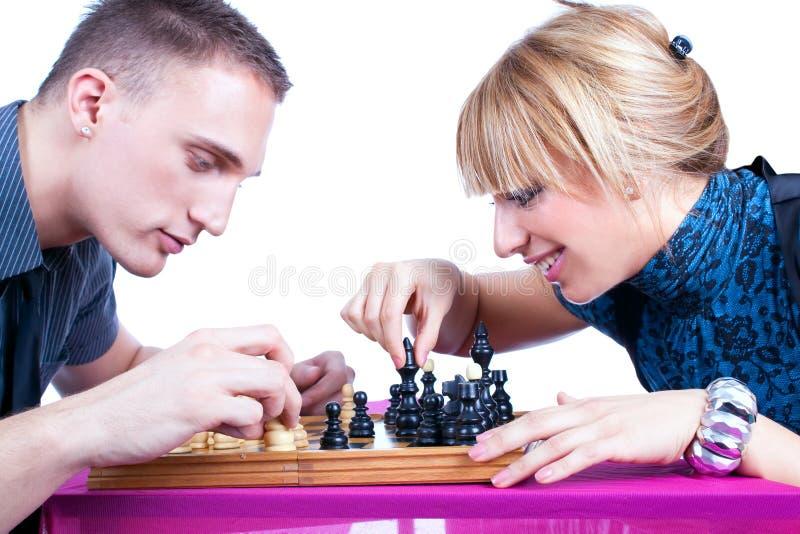 在家下棋的轻松的新夫妇 免版税图库摄影